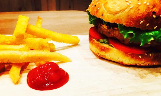Burger vegan avec steak de céréales et lentilles, sauce à l'avocat et frites de polenta